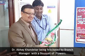 Dr. Abhay Khandekar being felicitated by Branch Manager with a Bouquet of Flowers